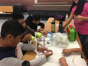 Robotics Club students working at a table on their project.