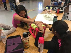 Girls sitting at a table, working on their robotics project.