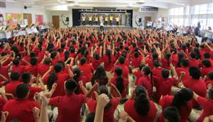 Excited students waving their hands in the air during Be Kind Assembly.