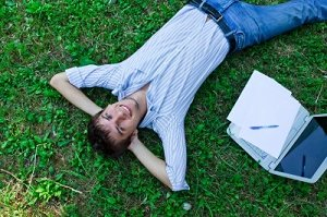 Young man on grass next to laptop
