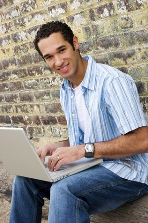 Boy on laptop in front of brick wall