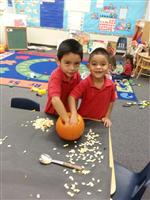 two boys cleaning out a pumpkin